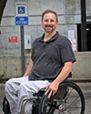 Photo of Eric Lantz in front of a handicap parking sign while sitting in his wheelchair