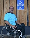 Photo of Michael Haynes in front of a handicap parking sign while sitting in his wheelchair