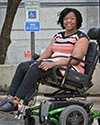 Photo of Regina Blye in front of a handicap parking sign while sitting in her motorized wheelchair
