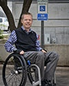 Photo of Chase Bearden in front of a handicap parking sign while sitting in his wheelchair