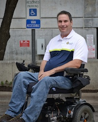 Photo of Mack Marsh in front of a handicap parking sign while sitting in his motorized wheelchair